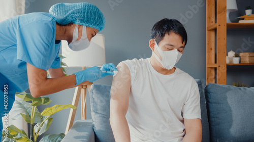 Fototapeta Young Asia lady nurse giving Covid-19 or flu antivirus vaccine shot to male patient wear face mask protection from virus disease sit on couch in living room at house. Vaccination concept. obraz