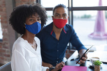 Smiling Mixed Race Man And African American Woman Wearing Face Mask Sitting, Using Tablet In Cafe
