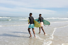 African American Brothers With Surfboards Running Towards The Waves At The Beach