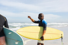 African American Senior Man With Surfboard Pointing Towards The Waves At The Beach
