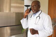 African American Senior Male Doctor Talking On Smartphone At Home