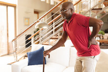 African American Senior Man With Back Pain Walking With A Walking Stick At Home