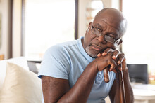 Stressed African American Senior Man Holding A Walking Stick Sitting On The Couch At Home