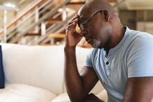 Stressed African American Senior Man With Hand On Head Sitting On The Couch At Home