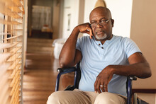 Stressed Disabled African American Senior Man Sitting On The Wheel Chair At Home