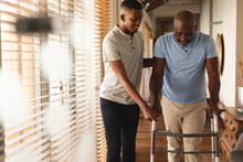 African American Young Man Helping His Father To Walk With Walking Frame At Home
