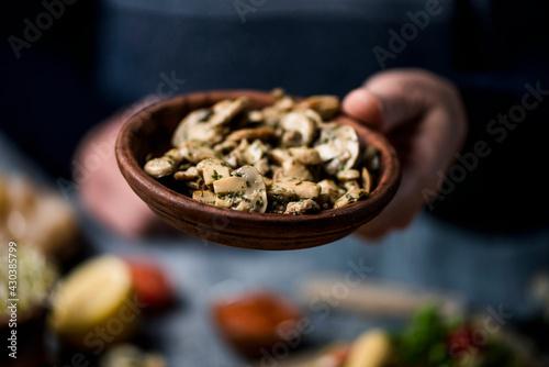 man brings a plate of fried mushrooms