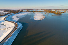 Aerial View Of Snow-covered Dike With Road On Top Along Flooded Floodplains Of River IJssel In Winter, Overijssel, Netherlands.