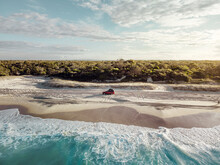 Aerial View Of A Car Driving On The Beach At Sunset, Bribie Island, Queensland, Australia.