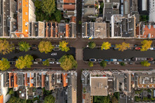 Aerial View Of Amsterdam Canal From Top, View Of Several Boat Anchored Along The River In City Downtown, Amsterdam, The Netherlands.