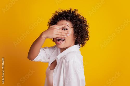 Slika na platnu Young smiling african girl hand cover eyes pekk through fingers posing on yellow