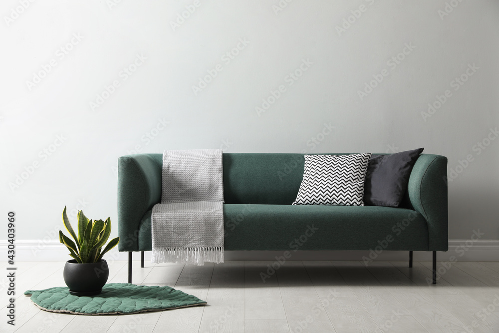 Obraz Stylish living room interior with comfortable green sofa and beautiful plant fototapeta, plakat