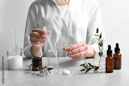 Scientist making cosmetic product at grey table in laboratory, closeup - fototapety na wymiar