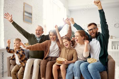 Happy big family celebrating goal while watching football match on tv - fototapety na wymiar