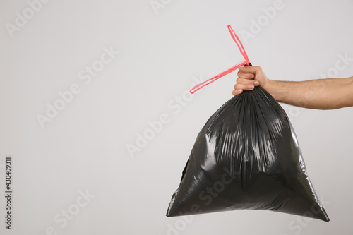 Obraz Man holding full garbage bag on light background, closeup. Space for text - fototapety do salonu