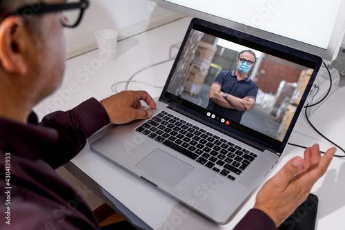 Fototapeta Dettaglio di un computer portatile nel cui schermo compare un uomo con la masche