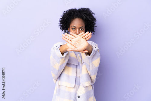Fotografia, Obraz Young African American woman isolated on purple background making stop gesture w