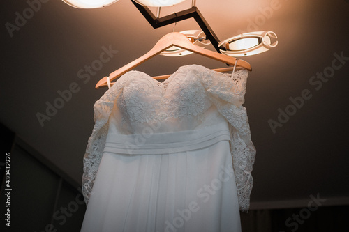 Canvas Wedding dress hanging on the chandelier in the room