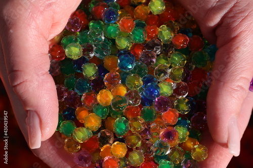 Obraz Small colorful plastic balls in the hands - fototapety do salonu