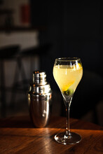 A Sweet And Sour Refreshing French 75 Sparkling Gin Cocktail In A Flute Glass, Olive Garnish, In Direct Hard Sunlight With Long Shadows, On A Wooden Table, Vertical Photo With Copy Space