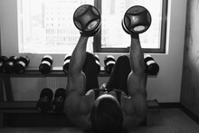 A Man With Big Muscles Is Engaged In Weightlifting In The Gym. A Pumped-up Athlete Goes In For Sports On Heavy Weight Simulators. Sport Exercises