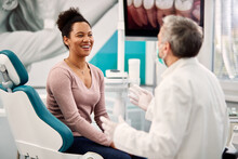 Happy Black Woman Talking To Her Dentist During Appointment At Dental Clinic.