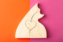 A Figurine Of Hugging Cats, Carved From Solid Pine By A Hand Jigsaw. On A Multi-colored Background