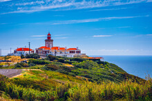 The Lighthouse In Cabo Da Roca. Cliffs And Rocks On The Atlantic Ocean Coast In Sintra In A Beautiful Summer Day, Portugal. Cabo Da Roca, Portugal. Lighthouse And Cliffs Over Atlantic Ocean.
