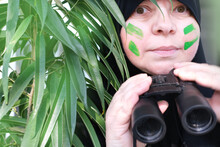 Close-up Curious Islamic Woman In War Paint, Holding Field Binoculars With Zoom, Peeping From The Bushes, Spying On Unfaithful Husband, Neighbors, Observation Of People And Animals