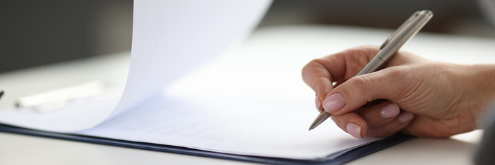 Woman writing with ballpoint pen in documents on clipboard in office closeup