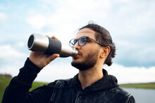 Portrait Of Young Man Drinking Water From Reusable Steel Thermo Bottle On Background Of Blurred Cloudy Sky. Wearing Glasses.