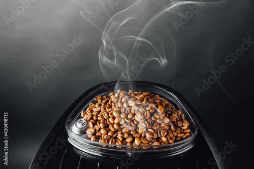 Canvas fresh roasted coffee beans with smoke in coffeemaker bean container, close-up vi