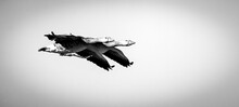 Grayscale Shot Of Two Geese Flying Under A Cloudy Sky - Great For Wallpapers