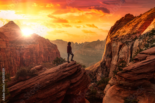 Adventurous Woman at the edge of a cliff is looking at a beautiful landscape view in the Canyon Poster Mural XXL