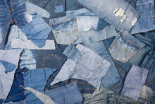 Old Denim Garbage Background. Recycling Old Jeans. Old Blue Jeans Ready For Recycling On Wooden Table. Denim Upcycle. Circular Economy. Pile Of Discarded Old Blue Jeans. Zero Waste