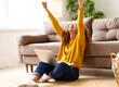 Leinwandbild Motiv Happy african american female celebrating success while working remotely or studying online at home
