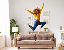 Happy African American Teen Girl Jumping On Sofa While Having Fun On Weekend At Home