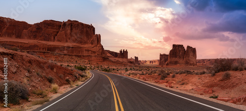 Fototapeta Panoramic landscape view of a Scenic road in the red rock canyons. Dramatic Colorful Sunset Sky Artistic Render. Taken in Arches National Park, located near Moab, Utah, United States. obraz