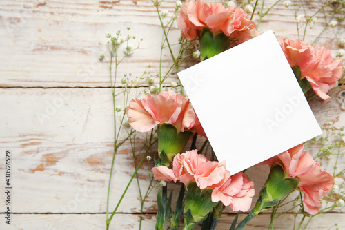 Fresh carnation flowers with empty paper sheet on white wooden background - fototapety na wymiar
