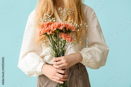 Fototapeta Young woman with beautiful carnation flowers on color background obraz