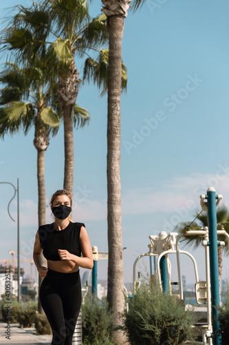 Fototapeta premium Athletic woman wearing face mask is running during her summer jogging workout