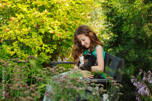 Valokuva happy kid girl relaxing in summer garden and playing with her cavalier king char