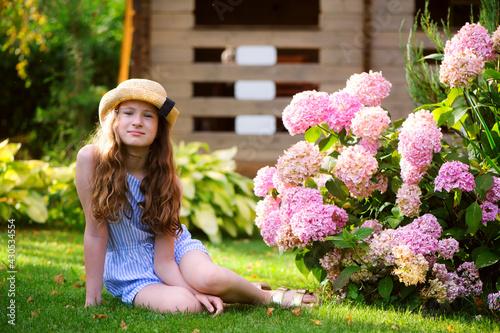 Fotografija happy kid girl walking in summer garden in straw, posing near pink hydrangea mac