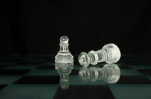 Clear Chess Piece Pawn And Fallen Queen Isolated On A Chequered Chess Board With A Black Background