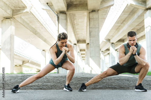 Athletic couple warming up during street workout - fototapety na wymiar