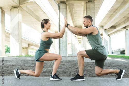 Athletic and happy couple doing lunges during street workout - fototapety na wymiar