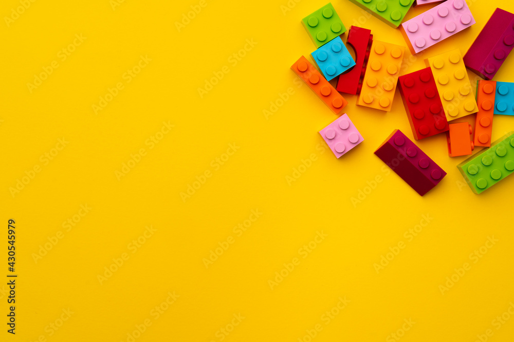 Kids toy constructor details scattered on yellow background - obrazy, fototapety, plakaty