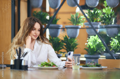 Side view of pensive beautiful woman sitting at the table with tasty salad and chatting with friends on modern phone. Concept of free time and communicating with followers online.  - fototapety na wymiar