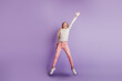 Small girl jump up catch isolated on purple background