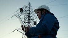 Woman Power Engineer In White Helmet Checks Power Line Using Computer On Tablet, Remote Control Of Power System. High Voltage Electrical Lines At Sunset. Distribution And Supply Of Electricity. Energy
